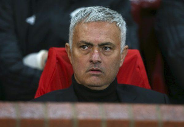 Mourinho, sentado no banco de reservas, com cara de poucos amigos
